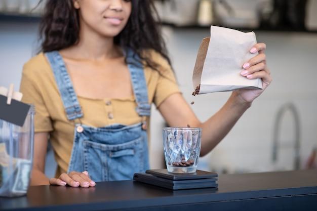 Gewicht, koffiebonen. vrouwelijke hand koffiebonen uit papieren zak gieten in glazen maatbeker, onderste deel van gezicht is zichtbaar