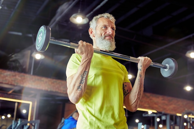 Gewicht training sterke volwassen man in sportkleding tillen gewogen bar of barbell op sportschool