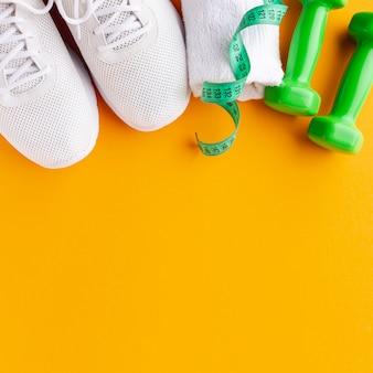 Gewichten en sneakers op diepgele achtergrond met kopie ruimte