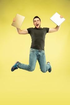 Gewichtloos. volledig lengteportret van gelukkige springende mens met gadgets die op gele achtergrond worden geïsoleerd. moderne technologie, concept van vrijheid van keuzes, concept van emoties. tablet gebruiken voor selfie of vlog tijdens de vlucht.