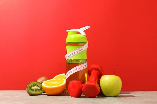 Gewichtsverlies accessoires op grijze tafel tegen rode achtergrond
