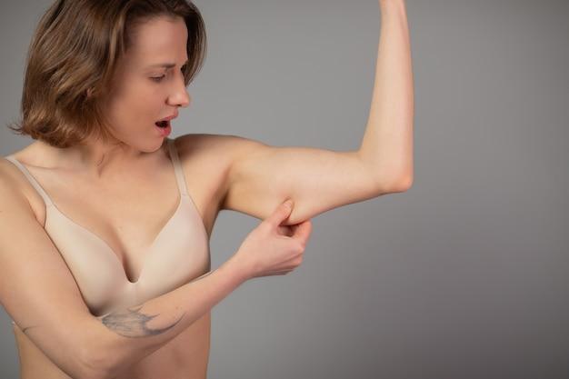 Gewichtsverlies concept. mollige vrouw knijpen bovenarm vet geïsoleerd op grijs.