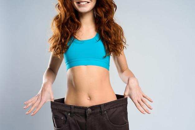 Gewichtsverlies concept. te grote broek voor meisje.