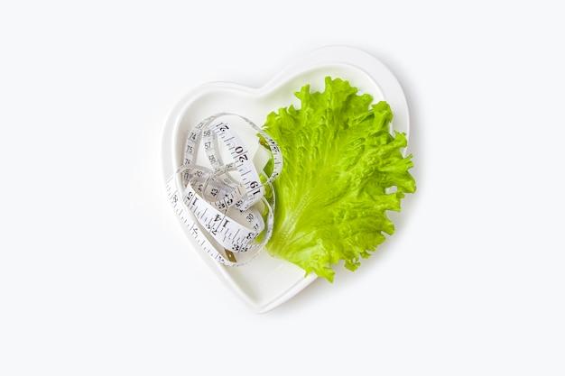 Gewichtsverlies dieet. de verse groene bladsla en het meten van band op hart vormden plaat op witte achtergrond.
