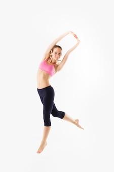 Gewichtsverlies fitness vrouw springen van vreugde. kaukasisch vrouwelijk model dat op witte achtergrond in volledig lichaam wordt geïsoleerd