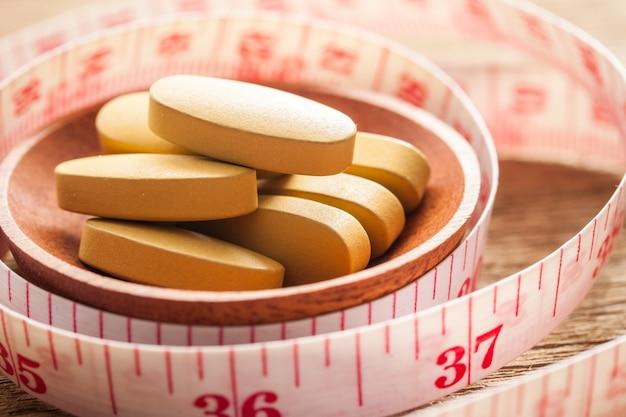 Gewichtsverlies vitamine en meetkabel op houten textuur, gezonde voeding concept