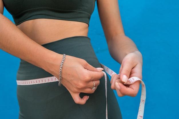 Gewichtsverliesconcept, slanke vrouw die haar dunne taille meet over blauwe achtergrond. gezond levensstijlconcept