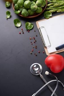 Gewichtsverliesweegschaal met centimeter, stethoscoop, halter, klembord, pen. dieet concept.