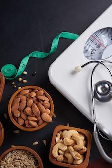 Gewichtsverliesweegschaal met centimeter, stethoscoop, klembord, pen. dieet concept. verschillende noten, sesamzaadjes. concept afslankdieet.