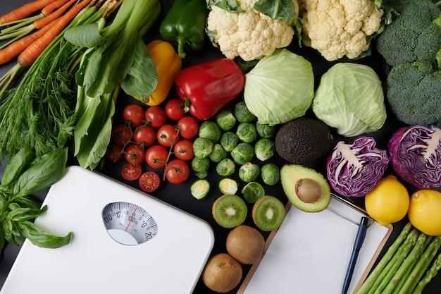 Gewichtsverliesweegschaal met groenten en fruit. dieet concept. bovenaanzicht.