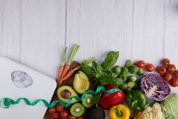 Gewichtsverliesweegschaal met verschillende soorten fruit en groenten. bovenaanzicht.