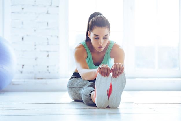 Gewijd aan fitness. vooraanzicht van mooie jonge vrouw in sportkleding die zich uitstrekt terwijl ze op de vloer voor het raam in de sportschool zit