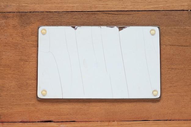 Gewiste en vuile voertuignummerplaat op houten lijstachtergrond.