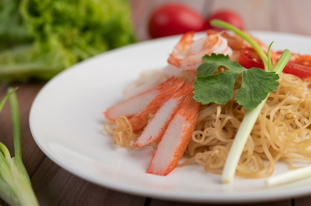 Gewokte instant noodle met garnalen en krabstick in een witte schotel.