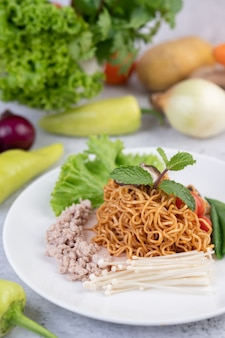 Gewokte noedels met varkensgehakt, edamame, tomaten en champignons in een witte plaat.