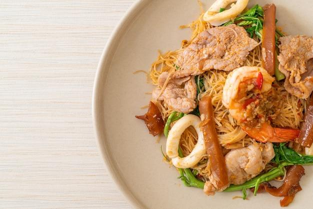 Gewokte rijstvermicelli en watermimosa met gemengd vlees - asian food style