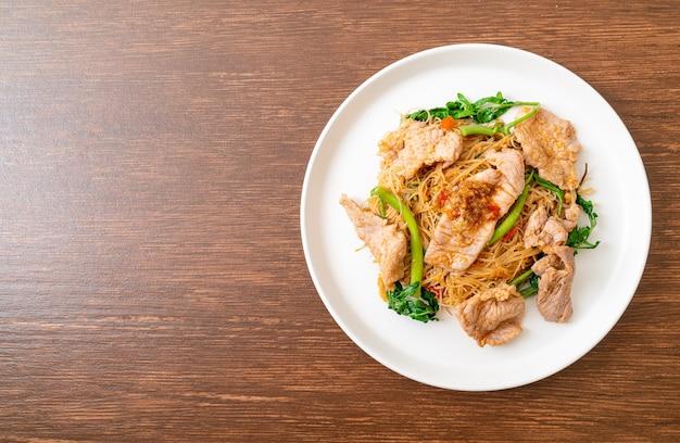 Gewokte rijstvermicelli en watermimosa met varkensvlees - asian food style