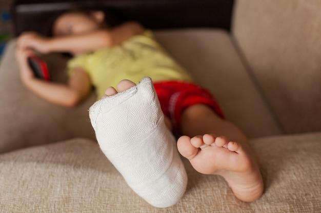 Gewond been van een tienermeisje in het gips dat thuis op de bank ligt en iets speelt of kijkt op haar mobiele telefoon