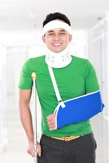 Gewonde jonge man gebruik kruk en arm slinger