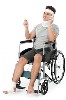 Gewonde jonge man in rolstoel praten aan de telefoon