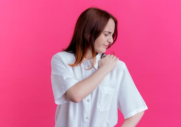 Gewonde jonge roodharige meisje greep schouder geïsoleerd op roze muur