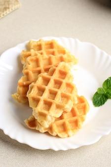 Gewone croffle croissant wafel op witte palte, crème tafel met muntblad. deze snack populair in zuid-korea