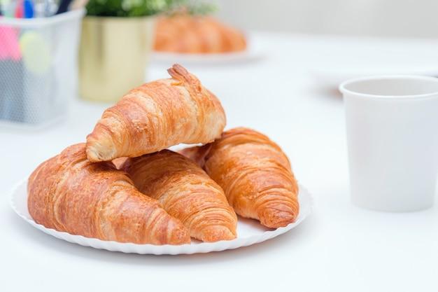Gewone croissants boven elkaar op het bord op de kantoortafel.