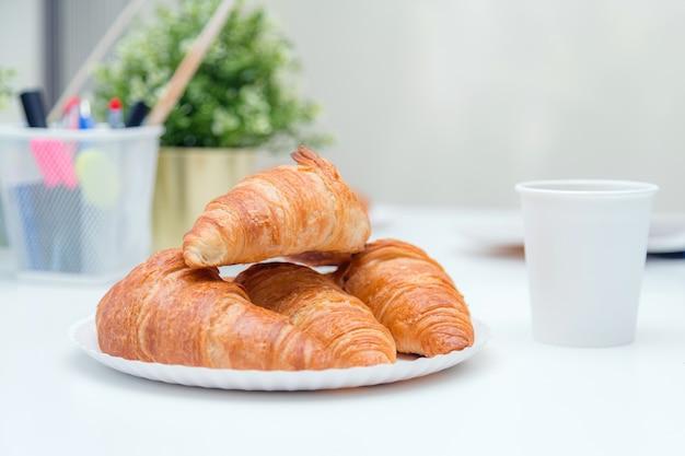 Gewone croissants bovenop elkaar op het bord, op witte tafel