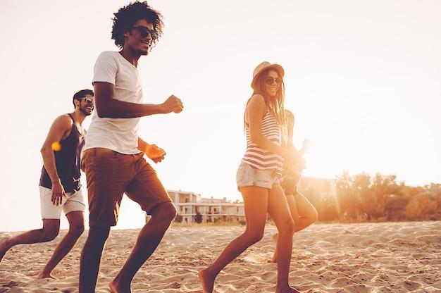 Gewoon blijven rennen! groep jonge vrolijke mensen die langs het strand rennen en er gelukkig uitzien