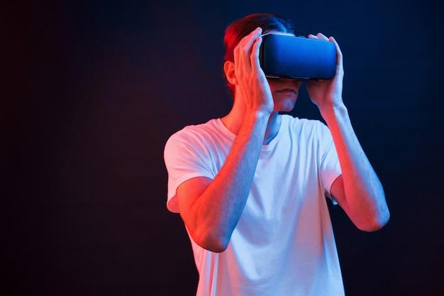 Gewoon de bril opzetten. jonge man met behulp van virtual reality-bril in de donkere kamer met neonverlichting
