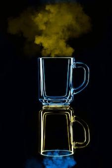 Gewoon een glas op een zwarte achtergrond met een reflectie. blauw en geel, met stoom. geïsoleerd.