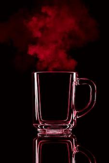 Gewoon een glas op een zwarte achtergrond met een reflectie. rode kleur, met stoom. geïsoleerd.