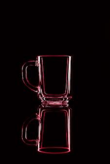 Gewoon een glas op een zwarte achtergrond met een reflectie. rode kleuren. geïsoleerd.