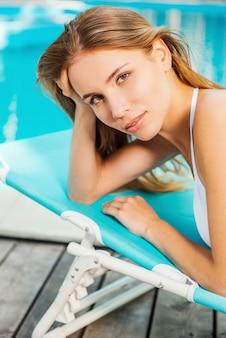 Gewoon een hemelse vakantie. mooie jonge vrouw in witte bikini die naar de camera kijkt en glimlacht terwijl ze ontspant in een ligstoel bij het zwembad