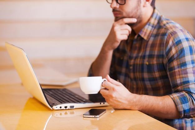 Gewoon geïnspireerd. bijgesneden afbeelding van een bedachtzame jonge man die op een laptop werkt en koffie drinkt terwijl hij in de coffeeshop zit