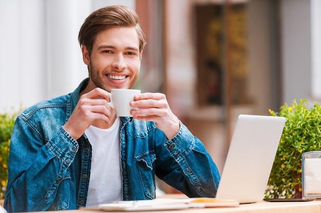 Gewoon geïnspireerd. glimlachende jonge man die een kopje koffie vasthoudt terwijl hij in een café zit