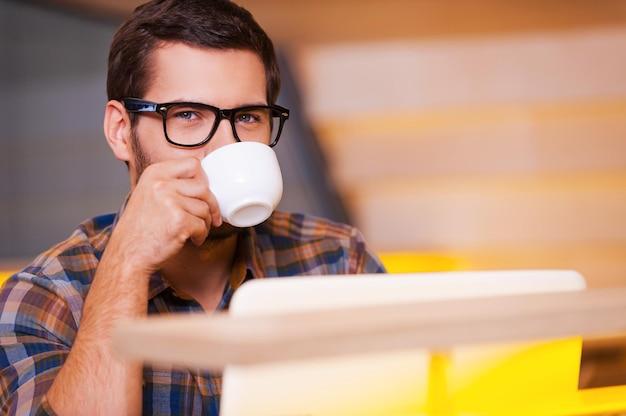 Gewoon geïnspireerd. knappe jongeman die koffie drinkt en naar de camera kijkt terwijl hij in de coffeeshop zit