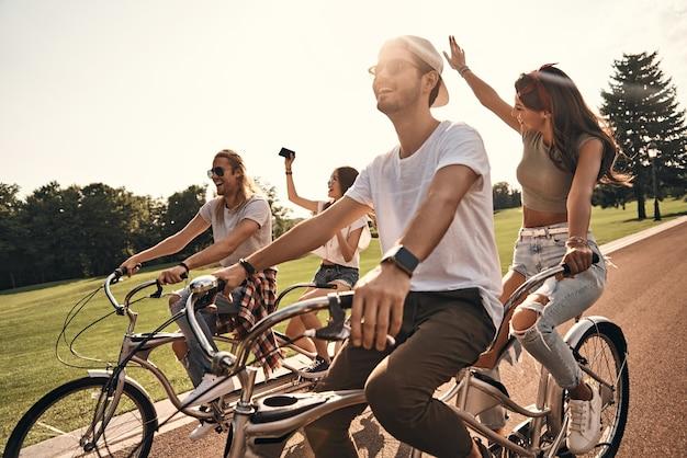 Gewoon lol hebben. groep gelukkige jonge mensen in vrijetijdskleding die selfie nemen en glimlachen terwijl ze samen buiten fietsen
