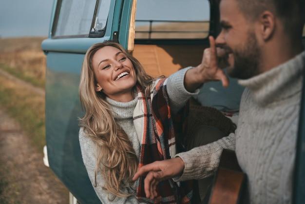 Gewoon lol hebben. mooie jonge vrouw haar vriendje neus aanraken en glimlachen zittend in de buurt van de retro-stijl minibusje