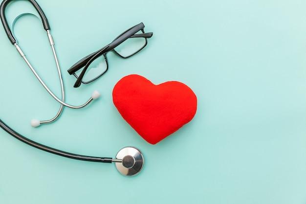 Gewoon minimaal ontwerp geneeskunde apparatuur stethoscoop bril en rood hart geïsoleerd op trendy pastel blauwe achtergrond