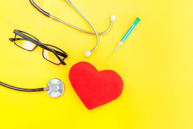 Gewoon minimaal ontwerp geneeskunde apparatuur stethoscoop bril spuit rood hart geïsoleerd op trendy gele achtergrond