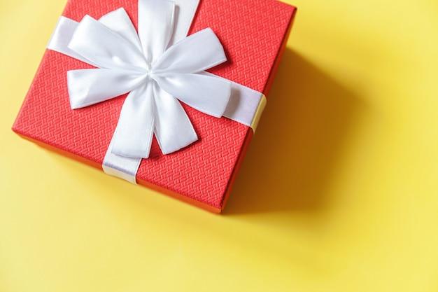 Gewoon minimaal ontwerp rode geschenkdoos geïsoleerd op gele kleurrijke achtergrond