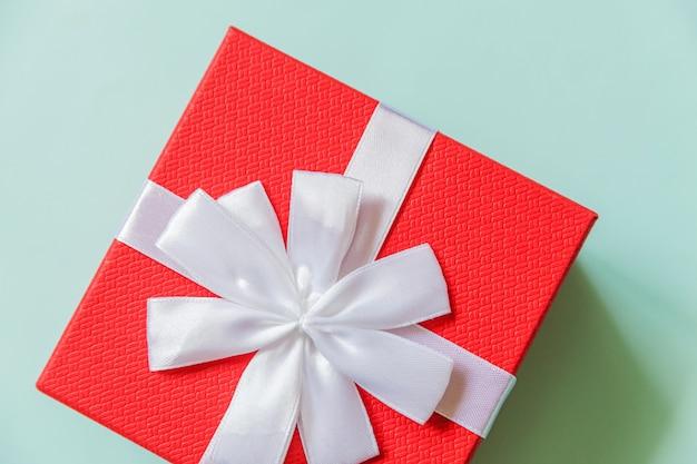 Gewoon minimaal ontwerp rode geschenkdoos geïsoleerd op pastel blauwe kleurrijke achtergrond