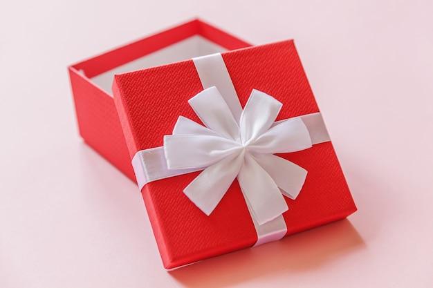 Gewoon minimaal ontwerp rode geschenkdoos geïsoleerd op pastel roze kleurrijke achtergrond