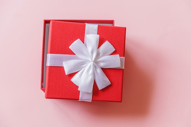 Gewoon minimaal ontwerp rode geschenkdoos geïsoleerd op roze achtergrond