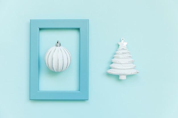 Gewoon minimale compositie winter objecten ornament fir tree bal in blauw frame geïsoleerd op blauwe pastel trendy achtergrond. kerstmis nieuwjaar december tijd voor viering concept. plat lag bovenaanzicht