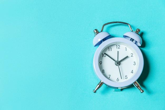 Gewoon minimalistisch design rinkelende twin bell vintage klassieke wekker geïsoleerd op pastel blauwe achtergrond