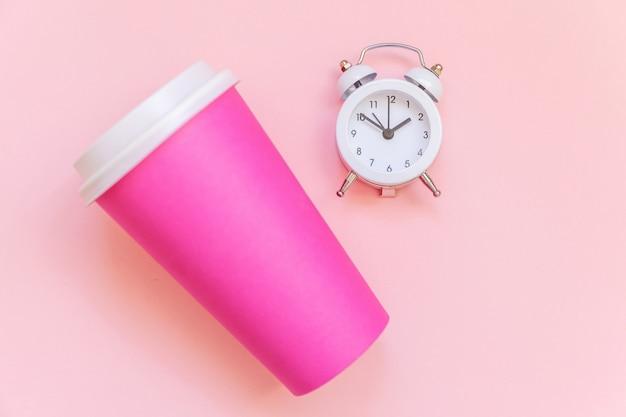 Gewoon plat lag ontwerp roze papieren koffiekopje en wekker geïsoleerd op roze pastel kleurrijke achtergrond