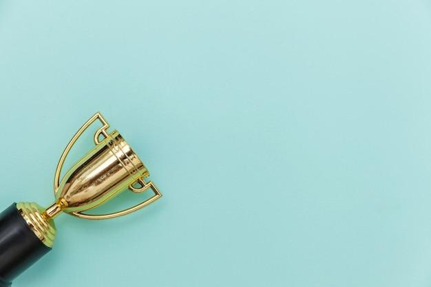 Gewoon plat leggen ontwerp winnaar of kampioen gouden trofee beker geïsoleerd op blauwe pastel kleurrijke achtergrond