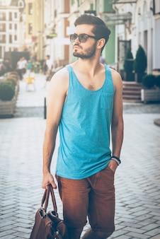 Gewoon rondlopen. knappe jongeman in een draagtas met vrijetijdskleding en wegkijkend terwijl hij over straat loopt